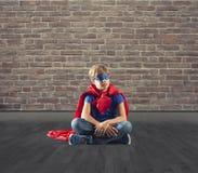 De zitting van het Superherojonge geitje op een muur die droomt royalty-vrije stock fotografie