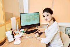 De zitting van het tandartsmeisje bij de lijst bij de computer en maakt een verslag royalty-vrije stock afbeeldingen