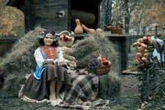 De zitting van het tienermeisje in hooi die een kroon en een nationaal Oekraïens kostuum naast de fruitmand dragen royalty-vrije stock fotografie