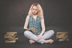 De zitting van het tienermeisje op de vloer naast boeken en emotioneel het tonen van haar haat, haat en moeheid stock foto's
