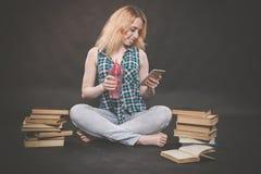 De zitting van het tienermeisje op de vloer naast boeken, wil niet leren, het drinken sap en het nemen van een selfie op smartpho stock foto
