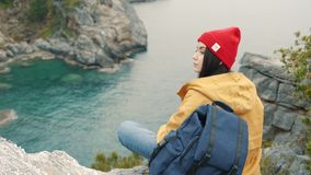 De zitting van het toeristenmeisje op de rand van een klip in de lagune en geniet van een mooie mening stock videobeelden