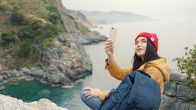 De zitting van het toeristenmeisje op de rand van een klip in de lagune en het schieten van selfie video stock videobeelden