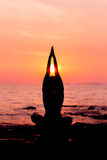 De zitting van het vrouwensilhouet in yoga stelt op overzeese terug aangestoken achtergrond Stock Afbeelding