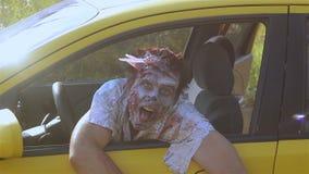 De zitting van het zombiemonster achter het wiel van de auto en de golvende handen stock video