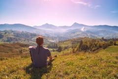 De zitting van de jonge mensenwandelaar op een heuvel in een groen gras Stock Afbeeldingen