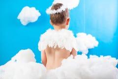 De zitting van de jongensengel in de wolken stock afbeelding
