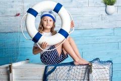 De zitting van de meisjezeeman en levensonderhoudreddingsboei Stock Fotografie