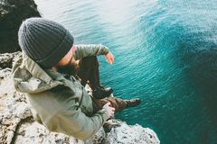 De zitting van de mensenreiziger bij klip het alleen denken boven diepzee Stock Afbeelding