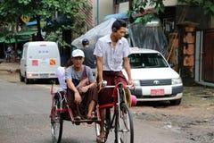 De zitting van de Myanmaresepassagier op de fietstaxi met drie wielen in de straat van Yangon stock foto