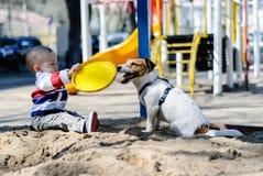 De zitting van de peuterjongen in zandbak bij speelplaats het spelen met hond` s stuk speelgoed Stock Afbeeldingen