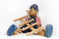 De zitting van Pinocchio op wit royalty-vrije stock foto