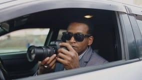 De zitting van de privé-detectivemens binnen auto en het fotograferen met dslrcamera stock foto