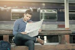 De zitting van de reizigersmens bij station en het kijken op kaart voor tra Stock Afbeelding