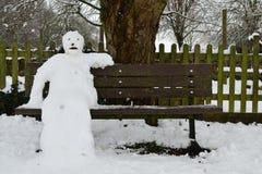 De zitting van de sneeuwmens op een parkbank Royalty-vrije Stock Fotografie