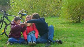 De zitting van de tienerjongen met mamma en papa op het gras Smartphone-Verslaving stock video