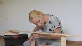 De zitting van de vrouwenhuisvrouw in de ruimte op de vloer, verzamelt houten die rek, in de opslag wordt gekocht Assemblage van  stock footage