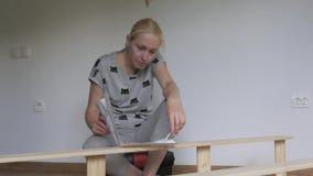 De zitting van de vrouwenhuisvrouw in de ruimte op de vloer, verzamelt houten die rek, in de opslag wordt gekocht Assemblage van  stock videobeelden