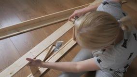 De zitting van de vrouwenhuisvrouw in de ruimte op de vloer, verzamelt houten die rek, in de opslag wordt gekocht Assemblage van  stock video