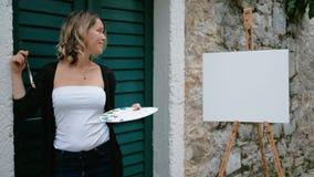 De zitting van de vrouwenkunstenaar op stappen van straat en trekt in verfstootkussen stock videobeelden