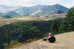 De zitting van de vrouwentoerist op berg Mening over Bergen en Omalo-dorp georgië royalty-vrije stock foto