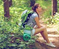 De zitting van de vrouwentoerist op halt in bos royalty-vrije stock foto