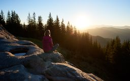 De zitting van de vrouwenwandelaar op kei in de bergen bij zonsondergang stock afbeelding