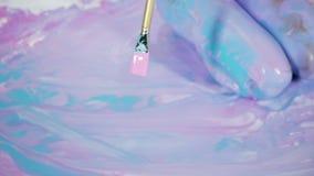 De zitting van de yogavrouw op een geschilderd canvas met abstracte patroon en verven stock video