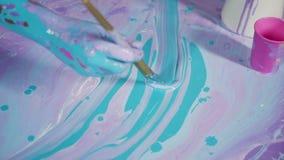 De zitting van de yogavrouw op een geschilderd canvas met abstracte patroon en verven stock videobeelden