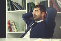 De zitting van de zakenman in bureau stock foto