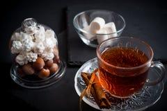 De zoete achtergrond van de de wintervakantie met diverse koekjes en kop van hete kruidige zwarte thee op donkere rustieke lijst Royalty-vrije Stock Foto