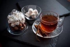 De zoete achtergrond van de de wintervakantie met diverse koekjes en kop van hete kruidige zwarte thee op donkere rustieke lijst Stock Afbeeldingen