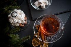 De zoete achtergrond van de de wintervakantie met diverse koekjes en kop van hete kruidige zwarte thee op donkere rustieke lijst Stock Foto's