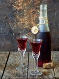 De zoete Amerikaanse veenbesalcohol drinkt likeur in twee glazen en fles op houten achtergrond royalty-vrije stock fotografie