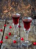 De zoete Amerikaanse veenbesalcohol drinkt likeur in twee glazen en fles op houten achtergrond royalty-vrije stock afbeelding