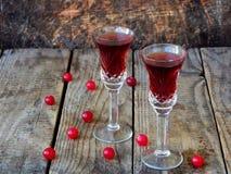 De zoete Amerikaanse veenbesalcohol drinkt likeur in twee glazen en fles op houten achtergrond stock fotografie