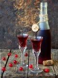 De zoete Amerikaanse veenbesalcohol drinkt likeur in twee glazen en fles op houten achtergrond royalty-vrije stock afbeeldingen