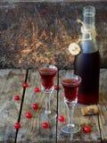 De zoete Amerikaanse veenbesalcohol drinkt likeur in twee glazen en fles op houten achtergrond stock foto's