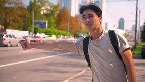 De zoete Aziatische jongen haalt de auto op de weg, glimlacht en toont steunen terwijl status op alleen weg, perfect stock footage