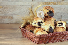 De zoete broodjes met papaverzaden liggen in een rieten mand Stock Afbeeldingen