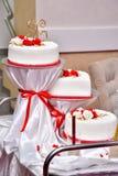 De zoete cakes in de vorm van rode rozen verfraaien de huwelijkscake met decoratievere takjes van witte room Stock Afbeeldingen
