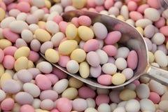 De zoete dalingen van het suikergoed op de close-up van de metaallepel royalty-vrije stock fotografie