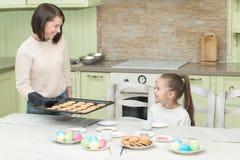 De zoete koekjes van het meisjesbaksel met haar moeder stock foto's