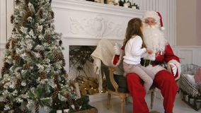 De zoete meisjezitting op Kerstman omwikkelt en beschrijvend hem wat zij voor Kerstmis wil stock foto's