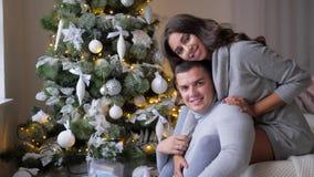 De zoete ogenblikken, meisje koestert echtgenoot en kijkt dichtbij op camera aan spar op vooravond van Kerstmis thuis stock videobeelden