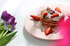 De zoete pannekoeken met aardbeien, kwark en kleurrijke suiker bestrooit stock fotografie