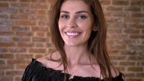 De zoete vrouw let op bij camera, het glimlachen, baksteenachtergrond stock footage
