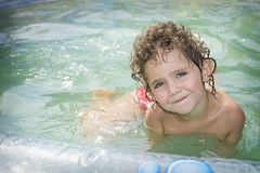 In de zomer in de binnenplaats in de pool zit kleine knap Royalty-vrije Stock Foto