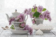 De zomer bloeiend boeket van sering en de kop van China met zwarte thee stock foto