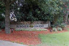 De zomer Brooke Neighborhood Sign Wall met buiten Gebladerte stock fotografie